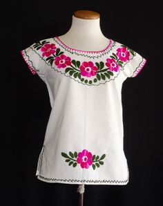 A wreath of beautiful, multi-tonal pink flowers adorn the neckline of this jalapa blouse.  The light-weight cotton manta fabric is sure to delight. Size X Small, fits size 2. Price: $34.00