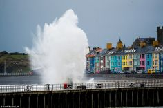 Swirling winds: Ferocious winds saw enormous waves crash into the pier atAberystwyth today after a sunny Good Friday