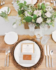 Bare wooden tables were set with woven rattan chargers, muslin runners, and etched Czech crystal glassware. The green and white centerpieces made by Fleur de V Events featured garden roses, sage, scabiosa, phlox, snowberries, and raspberry leaves.