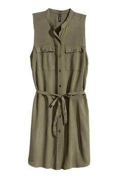 Košilové šaty bez rukávů: Krátké košilové šaty z viskózové tkaniny. Bez rukávů. Mají nízký stojáček, přední zapínání na knoflíky, patkové náprsní kapsy s knoflíkem, postranní kapsy a snímatelnou vázačku v pase. Bez podšívky. HM