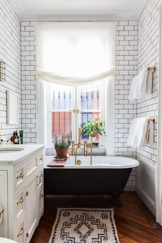 Bathroom with claw foot tub, white subway tile. White vanity, and dark wood floors.