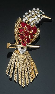 A Gem-set and Diamond Bird Brooch by Cartier  The stylised bird set with carved ruby body and emerald eye to the circular-cut diamond head and neck with textured wirework surround and articulated link graduated tail, circa 1950, with French assay and maker's mark, 6.5 cm high Signed Cartier, Paris