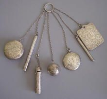 """B-arrow"" mark for Blackington (North Attleboro, Mass., 1862-1967) sterling chatelaine engraved with scrolls and flowers and the initials ""ELC"", mirror 1-1/2"", pillbox 3900 w/mirror 1-3/4"", dance cards 2"", coin ball 1"", lipstick 3996 2"", pencil 2-1/2"", case for ? 3"". Circa 1900."
