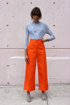 Orange wide leg trousers are worn with a light blue jumper.