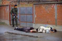 Bosnian Genocide ] A Serbian paramilitary soldier from Arkan's Tigers shoots Bosniak (Bosnian Muslim) civilians in the street of Bijeljina on 31 March 1992, the first day of the Bosnian war. Photographer: Ron Haviv (Genocid u Bosni, Genocid nad Bosnjacima)
