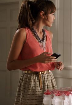 Revenge Ashley / Coral tank with tan and black printed skirt, gold skinny belt, and metal chain necklace / Season 1