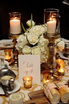 Centerpieces for round tables--low central arrangement with gold mercury glass pillar candle holders and gold mercury glass votive candles (Scott & Melissa Hopkins Photography):