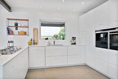Läckert designkök från Ballingslöv i öppen planlösning mot matsal och vardagsrum. Kök i vitt med installerad gasspis, kyl, frys, diskmaskin samt inbyggd ugn och kaffemaskin. KÖKSLUCKA: K2 Studio Ballingslöv