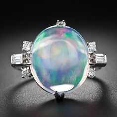 A high-cabochon opal, weighing 6.50 carats, looks as though it came from another planet. Luminous swirls of kaleidoscopic colors float inside a veritable crystal ball - a holograph on your finger! This special opal is embraced on each side by sparkling baguette and bright-white, full-cut diamonds set in platinum