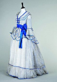 A blue and white striped gauze summer gown, circa 1870, the bodice with square neckline, flounced sleeves, peplum trimmed with blue satin, blue ribbon belt with later added bow.