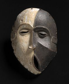 Mask, Idoma, early 20th century. Wood, chalk, kaolin, and carbon, 9 1/2 x 6 3/4 inches.
