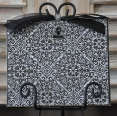 Black distressed frame.  Embellished with black and white printed paper and black bow.  Holds up to a 5x7 photo.  Black iron stand included.