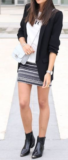 Trendy brunette is wearing an Aztec-print mini skirt and black fitted blazer. For a contrasting yet classic style combo, look no further than always reliable black and white.