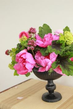 A compote centerpiece made up of peonies, ranunculi, scented geraniums, and viburnum