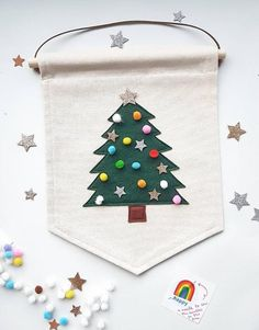 Decorate your own mini Christmas tree banner/wall hangingWool blend felt stitched onto fair trade, organic cotton with hardwood dowel top and vegan leather strap for hanging.This banner comes complete with a selection of mini multi colour pompoms, glitter stars and a needle, all ready to decorate yourself.Banner measures approximately 20 x 30cmPlease note these are decorations, not toys, please hang out of reach of young children.PLEASE SUPERVISE CHILDREN WITH NEEDLE AND LOOSE POM POMS AT… Pastel Colors, Colours, Wall Banner, Mini Christmas Tree, Make Ready, Glitter Stars, I Fall In Love, My Sunshine, To My Daughter
