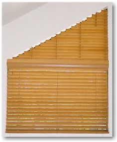 """The Blind Alley has decorated this angle-top window with 2"""" Country Woods blinds from Hunter Douglas"""
