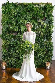 10 Unique Statement Walls for Your Wedding Decor | Since it is the Pantone Color of the Year, using greenery is the first on our list. This look is for the bride who is inspired by nature. Your wedding dress will pop beside this lush, dark green background. Try a few different shades of greenery to achieve that chic, minimalist vibe.
