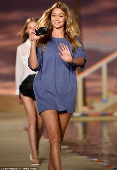 Role Reversal: Gigi brought a camera onto the catwalk with her as she modeled one look; sm...