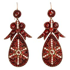 Victorian Bohemian Garnet and Seed Pearl encrusted earrings with large pendant drops surrmounted by bow form tops and gold wire backs, unsigned, late 19th Century