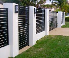 Заборы для частного дома: хитрости выбора стильного и функционального ограждения http://happymodern.ru/zabory-dlya-chastnogo-doma-33-foto-vidy-i-osobennosti-materialov/ Современный металлический забор с контрастными бетонными столбами