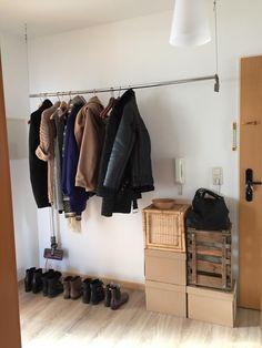 Frei hängende Kleiderstange als Aufbewahrungsort für Jacken und Mäntel im Flur. Improvisierter Schrank aus Kartons und Obstkiste.