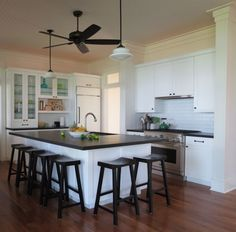 """Black & White Kitchen - From Maria Killam Blog - Kitchen Cabinets are SW7006 """"The lighting at night is so pretty.  Over the cabinets, underneath, and inside the glass cabinets. The appliances are integrated. And I especially love that the hood fan almost disappears, her appliances are GE Monogram."""""""