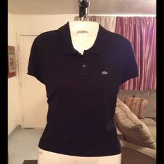"""Lacoste Polo Top Lacoste Women's Polo Top is made of 94% Cotton and 6% Elastane. Beautiful Top that fits great. The Color is Black. The Size is 42. The size translates to a Women's Size 10. The very last photo shows the Size chart for Lacoste Polo's from their website. Length """"22. Laying flat """"18. This item is in Good condition, Authentic and from a Smoke And Pet free home. All Offers through the offer button ONLY. I Will not negotiate Price in the comment section. Thank You😃 Lacoste Tops"""