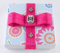 Reusable jewelry box. Decorate using scrapbooking paper and yarn, the secret is packing tape! Add strands of yarn to sticky side to create a ribbon.