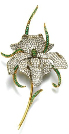 Emerald and diamond brooch Designed as an orchid, pavé-set with circular-cut emeralds and brilliant-cut diamonds.