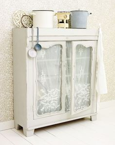 Vintage Cupboard. Pretty shabby chic accents all around from the lace covering to the enamel cookware.