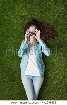 Young beautiful photographer girl lying on the grass, she is relaxing and holding a digital camera - Shutterstock Premier