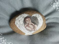 Painted rock,  baby in angelwings