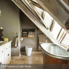 Die freistehende Badewanne unter der Dachschräge füllt den Platz optimal aus. Die alte Holzbalkendecke und die klassische Badewanne aus Gusseisen harmonieren  …