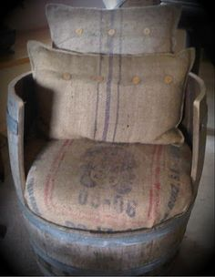 A seat from an old barrel and some vintage feed-sack cushions