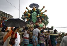 The idol of Durga is being loaded onto a boat to transport it through the waters of river Ganga to a pandal in Kolkata.