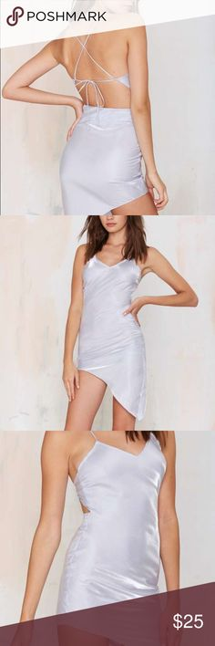 NWT Nasty Gal Silver Asymmetrical Slip Dress Super shimmery slip! Actually more reflective than the photos. It's gorgeous and the back ties together for an amazing effect. Tag says S but it runs small so it would fit XS best. Only selling because I think it's a bit too long for me. Nasty Gal Dresses Asymmetrical
