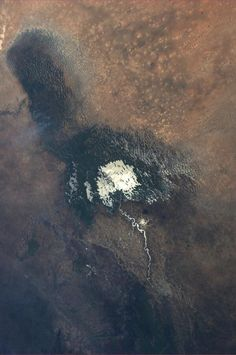"""Sun glint on shallow Lake Chad in Chad & Nigeria. October 17"", Astronaut Karen Nyberg. Beautiful ""painting"" shows dramatic scene: white stain is water remains, dark stain is vegetation on what used to be lake bed. Lake's water level has greatly decreased due to excessive irrigation and climate change."