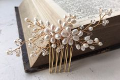 A pretty and simple wedding hair comb featuring ivory freshwater pearl flowers and crystals with pearl sprigs. Perfect for a simple hairstyle and also ideal for bridesmaids.  Available in gold or silver colour wire.  Approximate max length and width of detail: 10cm x 5cm. Complete with keepsake box to treasure forever.