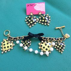 Betsey Johnson Earrings & Matching Charm Bracelet Betsey Johnson's jewelry is always fun. This Yellow & Black Polka Dot hearts Bracelet has a black satin bow and pearls accenting the yellow-black & black-yellow hearts on this charm bracelet. The matching Polka dot heart dangle pierced  earrings complete the look.   The earrings are on the original card and show their original price of  $35.  The bracelet was originally $75, but both are priced to sell at $70 for the set. Betsey Johnson…