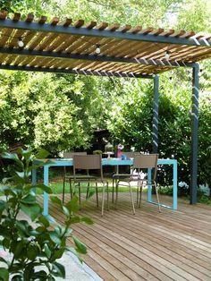 Pergola métal, terrasse bois et table de jardin design.                                                                                                                                                      Plus
