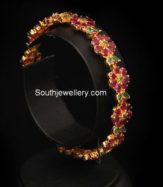 Bring color to your outfits with this distinguishing piece of jewellery. An enchanting floral bangle studded with rubies and emeralds in 22 carat gold. Wedding Jewelry Sets, Bridal Jewelry, Jewelry Design Earrings, Gold Jewellery, Antique Jewellery, Jewellery Designs, Jewelery, Ruby Bangles, Gold Bangles Design
