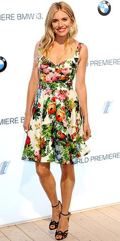 SIENNA MILLER Judging by the rose garden growing on her Dolce & Gabbana fit-and-flare dress, the actress has a green thumb when it comes to style. She finishes the look with unique strappy sandals, a pink lip and shoulder-grazing danglers at the BMW i3 Reveal Party in London.