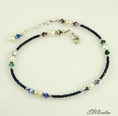 Handcrafted adjustable 10 1/4 - 10 3/4 inch beaded anklet created with blue and purple Charlotte iris seed beads, tanzanite, amethyst, emerald, blue Capri, sapphire, and violet assortment Swarovski Au