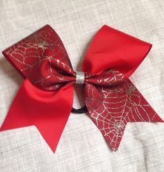 Large cheer bow red and silver spiderwebs. All of my cheer bows are attached to a high quality No Metal Goody Brand Hair Elastic. Cheer Bows are