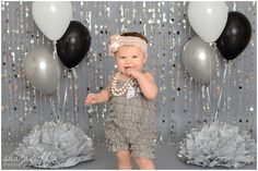 Shana Griffin Photography first birthday cake smash photo setup. Bead curtains, Salvage fashion grey paper, Pom poms, balloons, a romper and a cute headband!