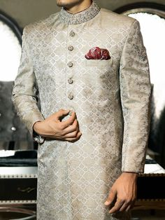 Junaid-jamshed-silver shade Another Jamawar fabric cloth that has been designed with block print all over the Sherwani. The Sherwani has consisted of hand embroidery on the collar, sleeves and on the buttons with a maroon puffed handkerchief. Mens Indian Wear, Mens Ethnic Wear, Indian Groom Wear, Indian Wedding Wear, Indian Men Fashion, Groom Fashion, Men's Fashion, Punjabi Wedding, Indian Weddings