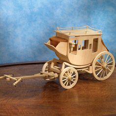 Old-west stagecoach model kit with pre-cut and numbered wooden pieces. Wooden Toy Cars, Wooden Wagon, Wooden Wheel, Wood Toys, Woodworking Patterns, Woodworking Projects, Toy Wagon, Wooden Model Kits, Chuck Wagon
