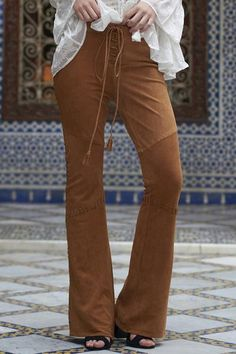 Gorgeous high rise flared suede pants in a rich camel color. Features lace up front closure with tassel ties, lace detailing on side seams and 2 back pockets. 100% lamb suede.
