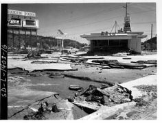 Baken Park Business and broken asphalt, the parking lot was full of merchandise. Rapid Creek runs along the backside of the shopping area. When the creek flooded, merchandise was forced out of store front filling the parking lot.