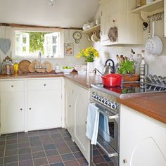 Bespoke Shaker-style kitchen units make the most of the limited space in this country-style room. Complete the look with cute accessories and traditional stone flooring. Kitchen, Plain English.